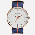 An image of the rose gold classic slim watch with a blue NATO strap sold by Brathwait.